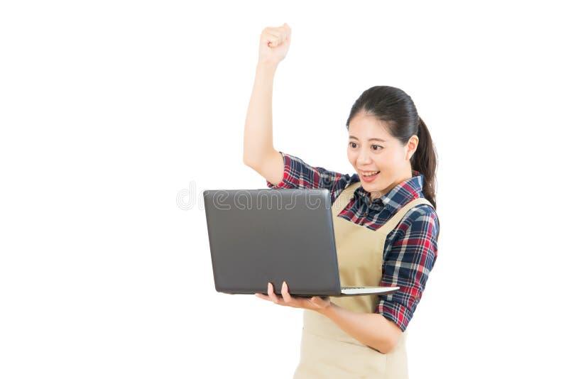 Ama de casa que usa el ordenador acertado fotografía de archivo libre de regalías