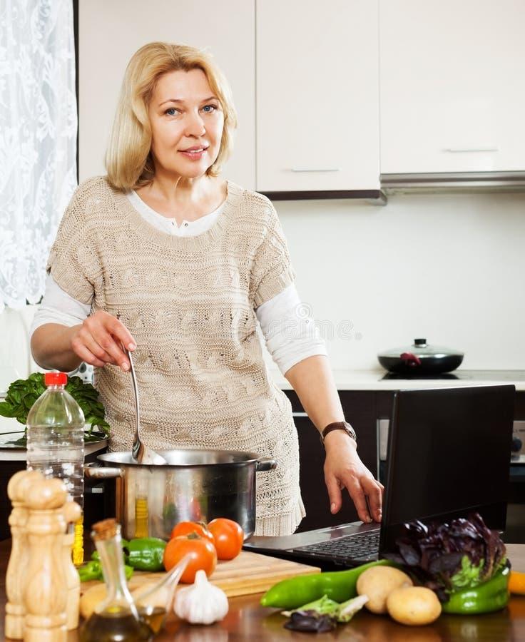 Ama de casa que usa el ordenador portátil mientras que cocina la sopa imagen de archivo libre de regalías