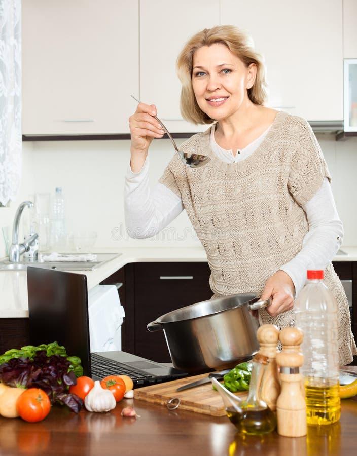 Ama de casa que usa el ordenador portátil mientras que cocina la sopa con la verdura fotografía de archivo