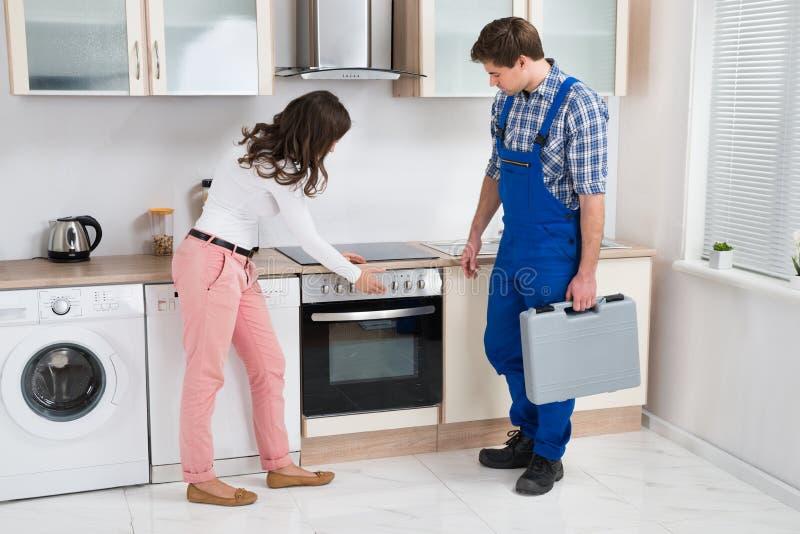Ama de casa Showing Damaged Oven To Worker imagen de archivo libre de regalías