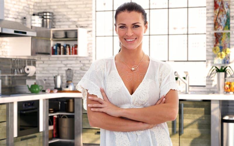Ama de casa sobre 40 en cocina en casa imagen de archivo