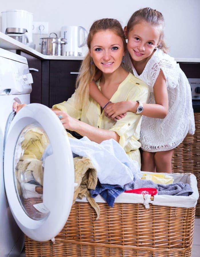 Ama de casa y muchacha que hacen el lavadero fotos de archivo libres de regalías