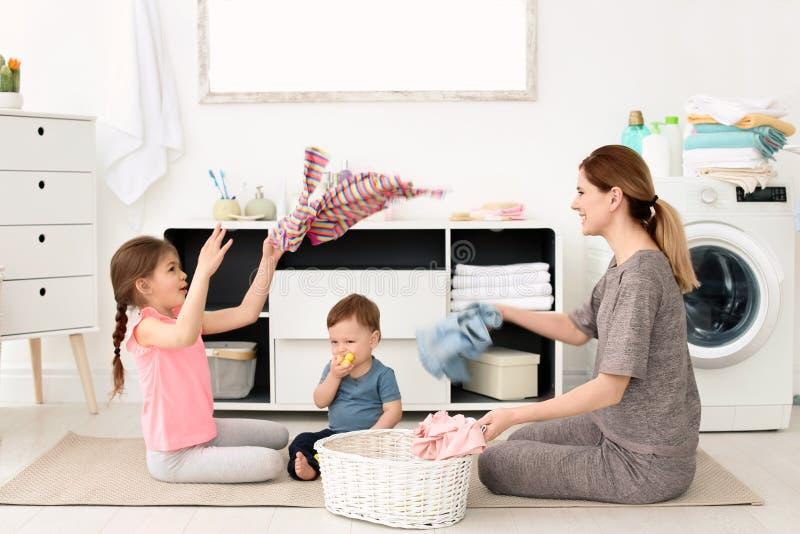 Ama de casa y niños que se divierten mientras que dobla recientemente imagen de archivo