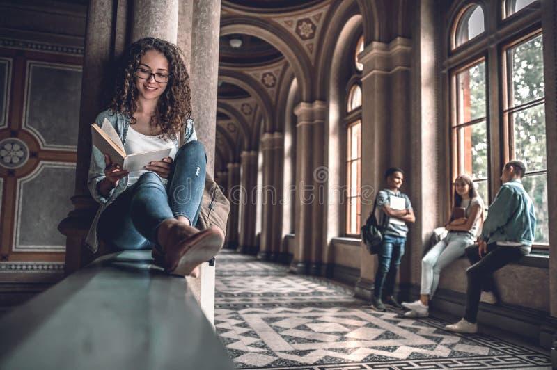 Ama ler Estudante fêmea bonito que senta-se nos trilhos na universidade e que prepara-se para exames, quando seus amigos imagens de stock