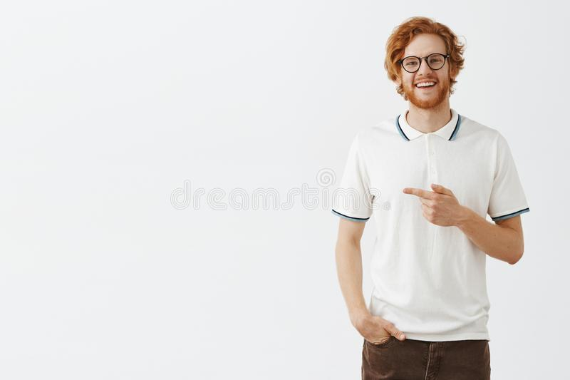 Amablemente mostrándonos gran oferta Retrato del modelo masculino del pelirrojo hermoso amistoso y feliz en señalar blanco del po fotografía de archivo libre de regalías