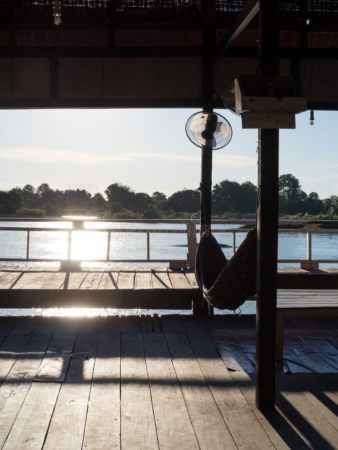 Amaca in casa di legno vicino al fiume prima del tramonto in laotiano fotografia stock libera da diritti