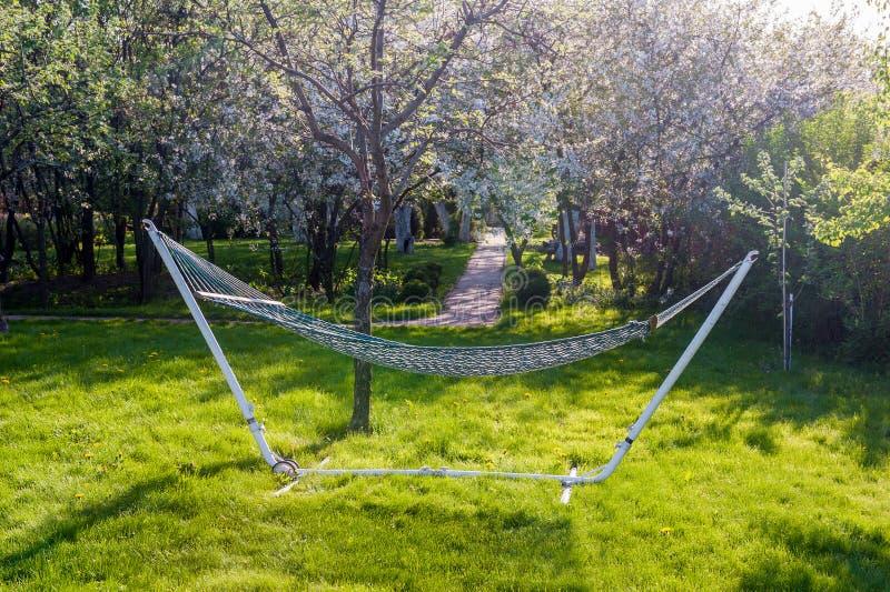 Amaca di vimini per la fine di campeggio - su sui precedenti del giardino di fioritura della molla un giorno soleggiato fotografie stock libere da diritti