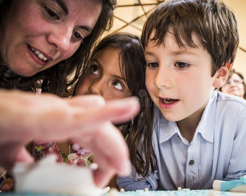 AMADORA/PORTUGAL-25 augustus-2015-moeder die kinderen helpen stock afbeeldingen