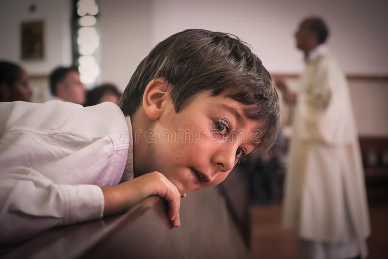 AMADORA/PORTUGAL- 25 de agosto de 2015 - criança na igreja com padre atrás imagem de stock royalty free