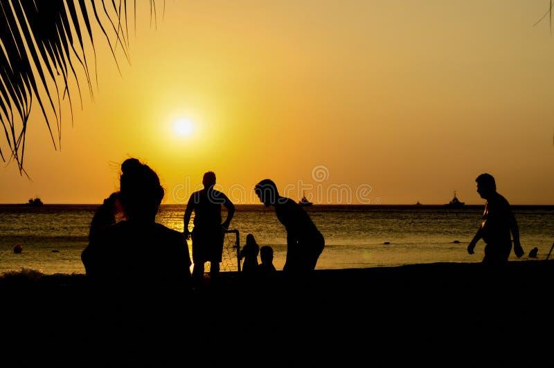 Amadores que jogam o futebol na praia de Jumeira em Santa Marta, Colômbia durante o por do sol fotografia de stock