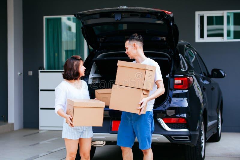 Amadureça caixas de cartão levando do casal asiático feliz do tronco de carro na casa nova imagens de stock