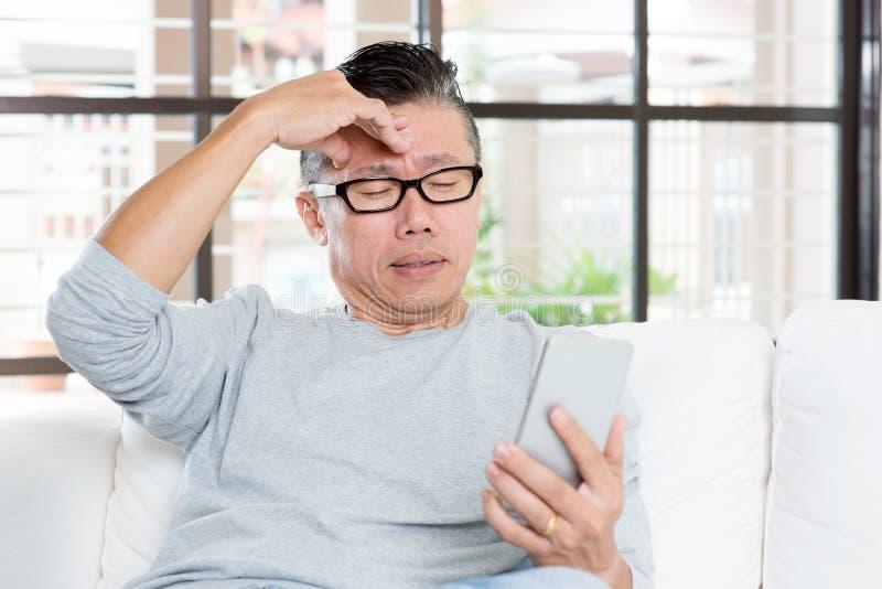Amadureça a dor de cabeça asiática do homem ao usar o smartphone imagens de stock royalty free