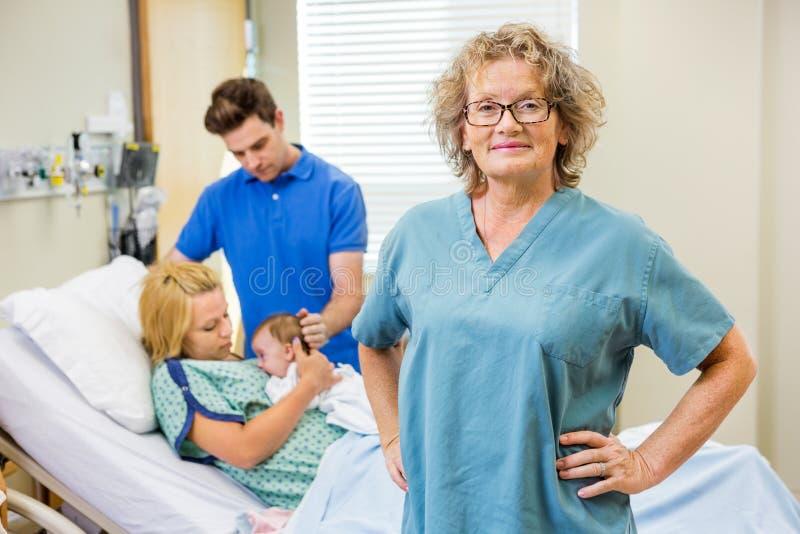 Amadureça a enfermeira Standing With Couple e o bebê recém-nascido foto de stock royalty free