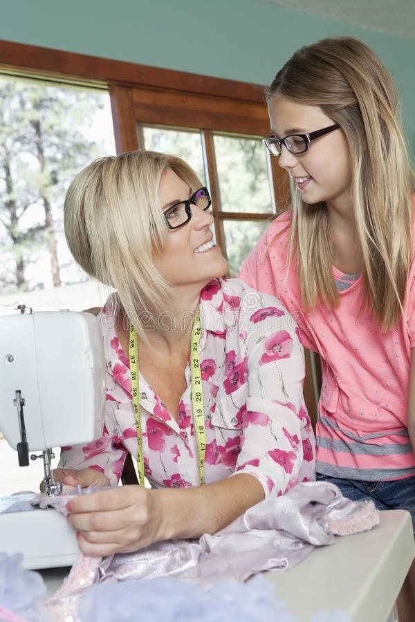 Amadureça a mãe que olha a filha ao costurar o pano fotografia de stock royalty free