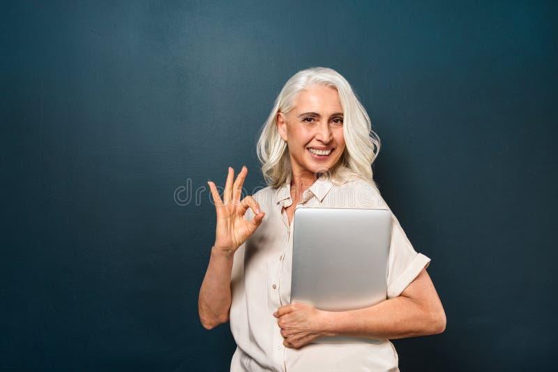 Amadureça a mulher adulta alegre que mostra o gesto aprovado que guarda o laptop fotografia de stock royalty free