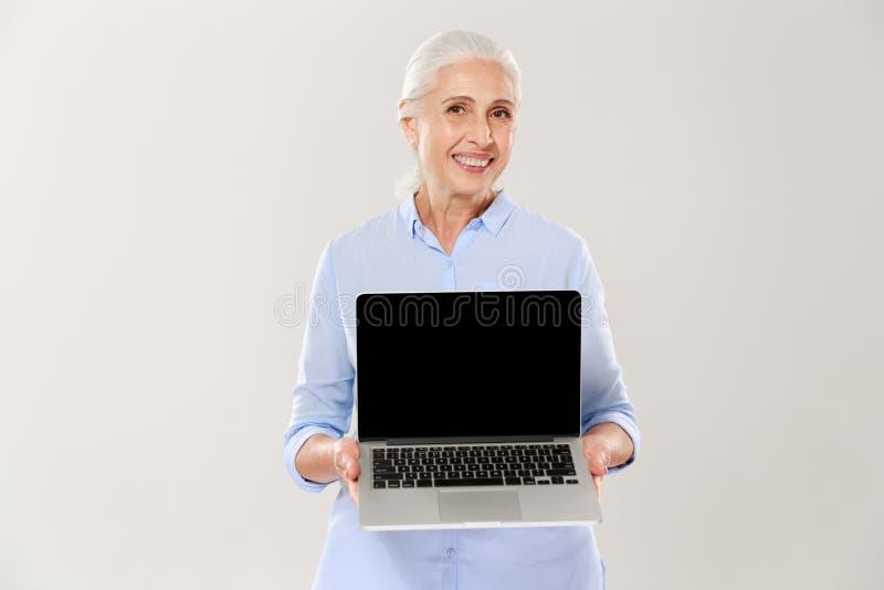 Amadureça a mulher cinzento-de cabelo que sorri e que mostra a tela vazia do portátil isolada foto de stock royalty free
