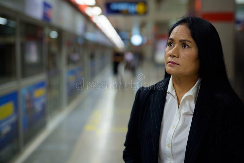 Amadureça a mulher de negócios asiática bonita dentro do sta do metro fotos de stock royalty free