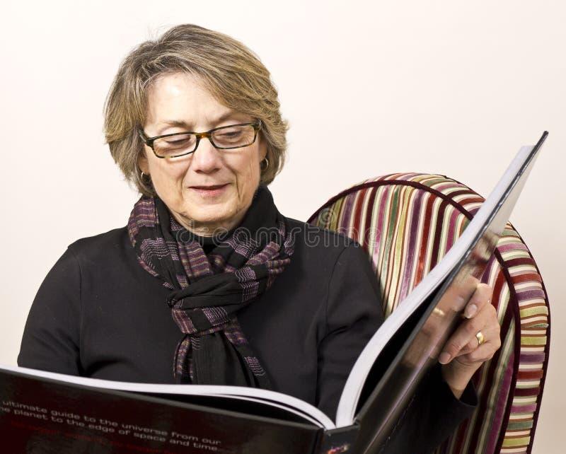 Amadureça a mulher que lê o grande livro imagem de stock