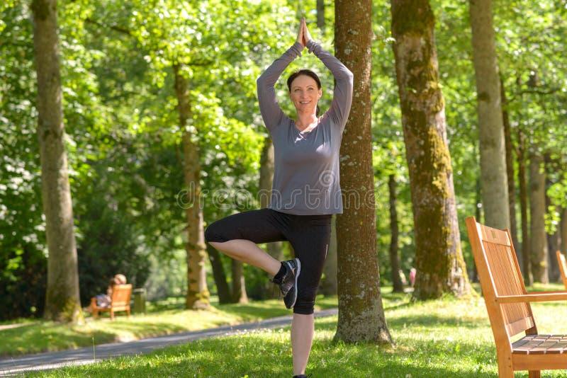 Amadureça a mulher que relaxa ao praticar a ioga fotografia de stock