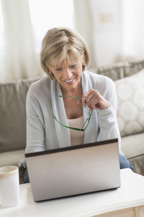 Amadureça a mulher que usa o portátil ao guardar vidros fotografia de stock royalty free