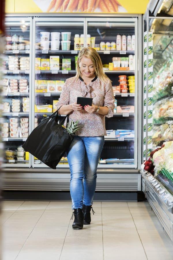 Amadureça a mulher que usa a tabuleta de Digitas ao andar no supermercado foto de stock royalty free