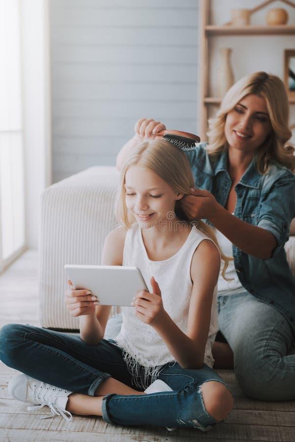 Amadureça o cabelo bonito da filha dos pentes louros da mãe, que olha a tabuleta imagens de stock