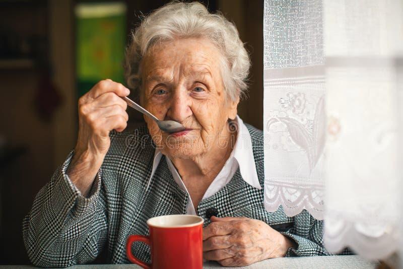 Amadureça o chá bebendo da mulher feliz na cozinha imagem de stock royalty free