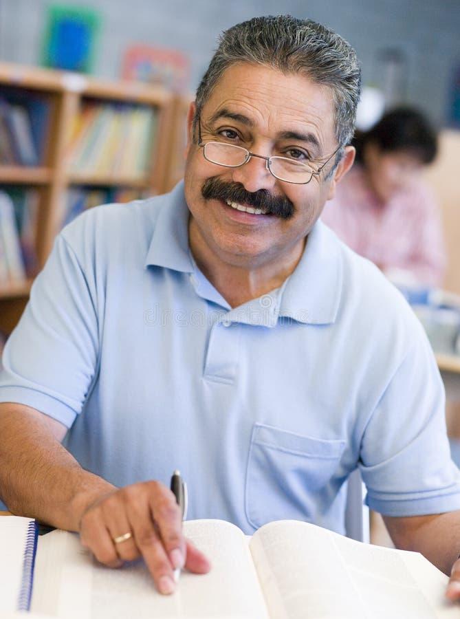 Amadureça o estudante masculino que estuda na biblioteca imagem de stock