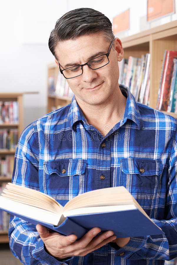 Amadureça o estudante masculino que estuda na biblioteca imagens de stock