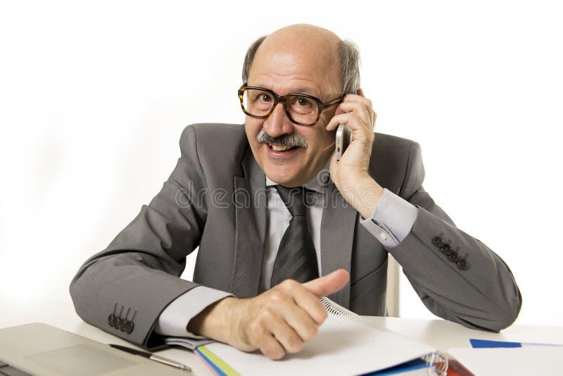 Amadureça o homem de negócio superior que fala no telefone celular no trabalho da mesa de escritório feliz e em gesticular engraç fotografia de stock