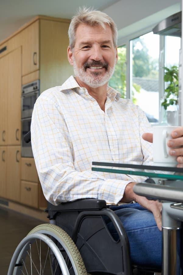 Amadureça o homem deficiente em casa com bebida quente imagens de stock royalty free