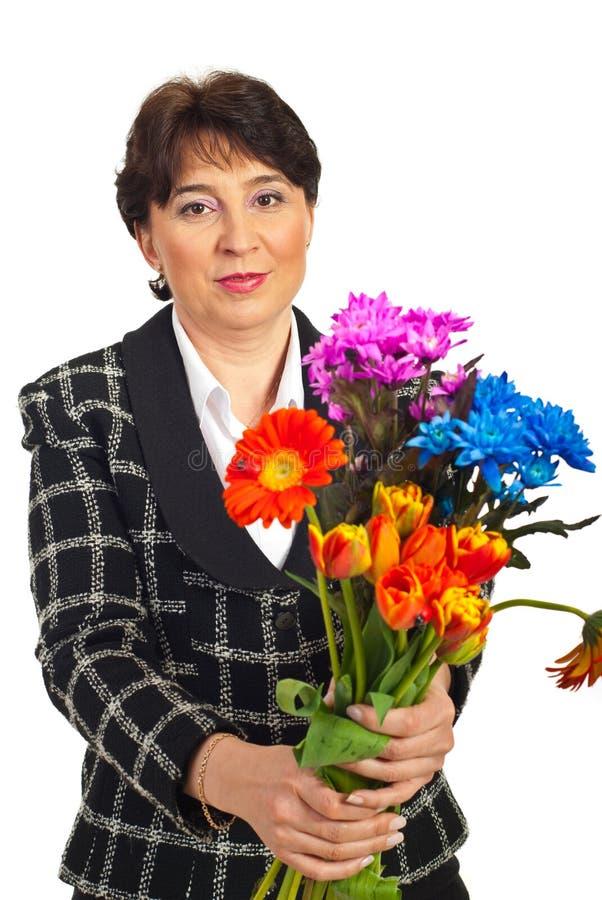 Amadureça o ramalhete de oferecimento das flores da mulher fotografia de stock royalty free