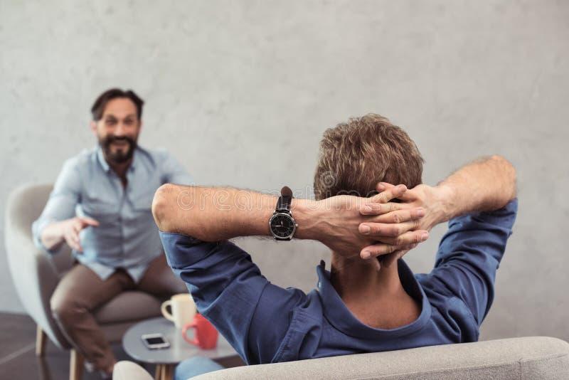 Amadureça os homens de negócios que falam ao sentar-se na ruptura de café imagens de stock royalty free
