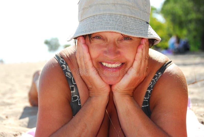 Amadureça a praia da mulher fotografia de stock
