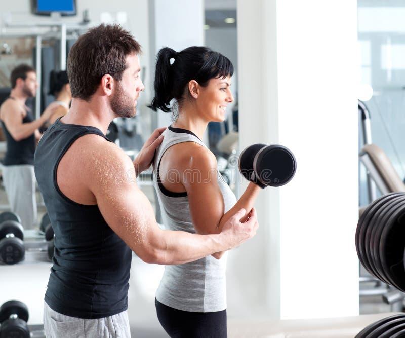 Amaestrador personal de la mujer de la gimnasia con el entrenamiento del peso foto de archivo libre de regalías