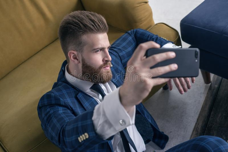 Amaizing look. Top view handsome young man in full suit taking selfie while sitting on the floor at home stock images