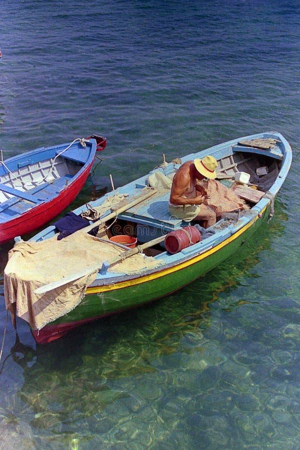AMALFI, ITALIEN, 1974 - älterer Fischer mit sachverständigen Handreparaturen das Netz auf Fischerboot im schönen Meer von Amalfi lizenzfreie stockbilder