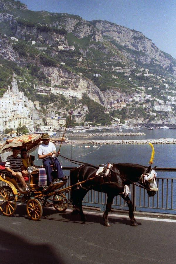 AMALFI, ITALIEN, 1992 - ein geduldiges Pferd zieht den Rollstuhl mit zwei Touristen an Bord und dem Kutscher im herrlichen Panora stockfotos