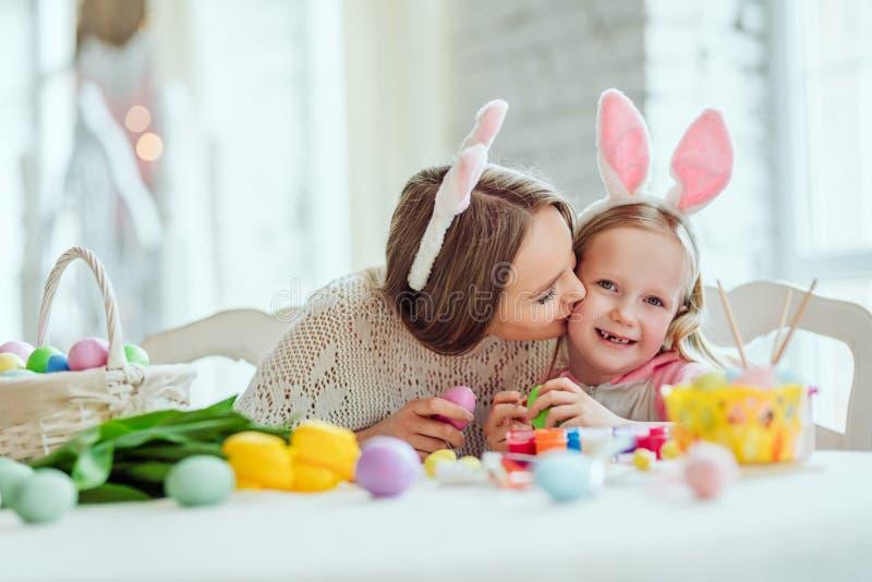 Amamos prepararnos para Pascua La mamá y la hija se están preparando para Pascua juntas En la tabla es una cesta con los huevos d fotografía de archivo