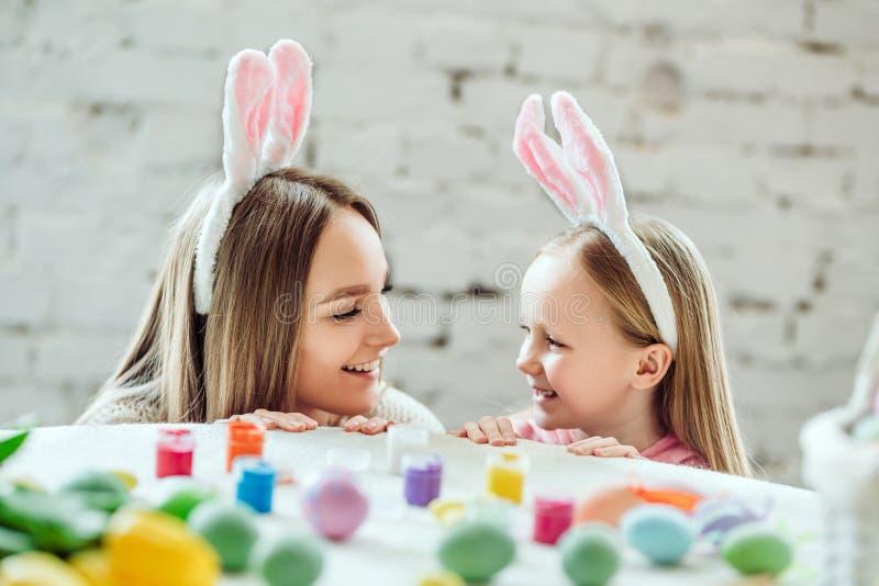 Amamos tradiciones hermosas Los huevos de la pintura de la mamá y de la hija, papá sostienen un conejo decorativo casero imágenes de archivo libres de regalías
