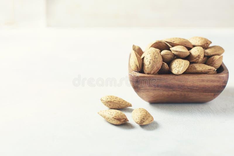 Amande crue dans les éviers dans une cuvette en bois sur un fond blanc, foyer sélectif Le concept de la nourriture saine photo stock