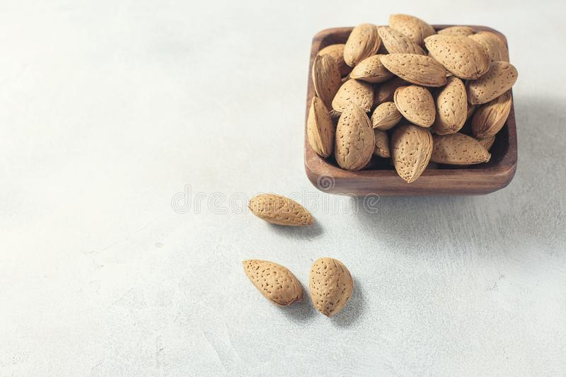 Amande crue dans les éviers dans une cuvette en bois sur un fond blanc, foyer sélectif Le concept de la nourriture saine images stock