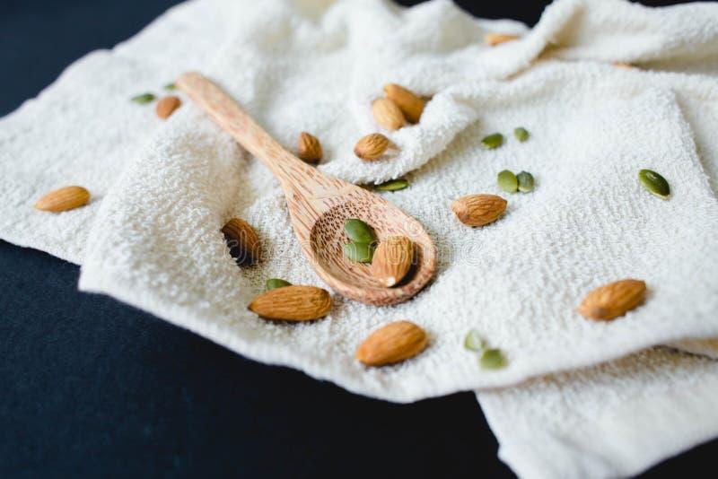 Amandelennoten op een natuurlijke rieten servet en bamboelepel stock foto's