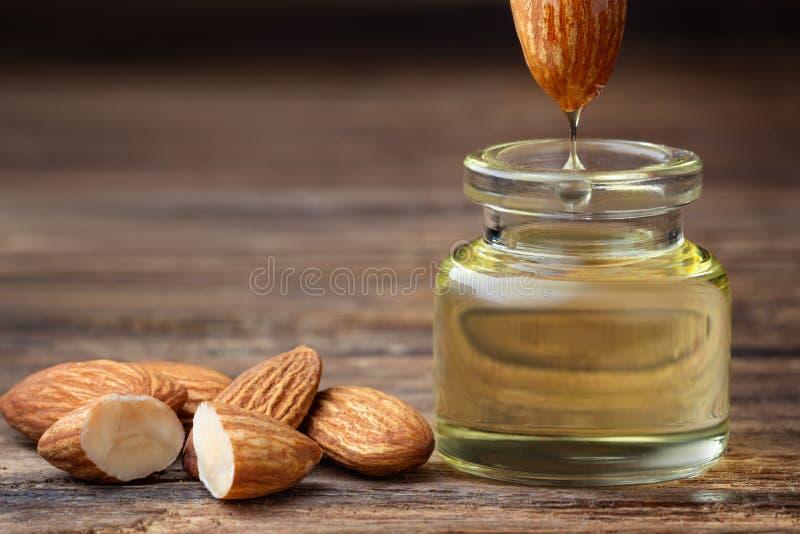 Amandelolie in fles en noten stock fotografie