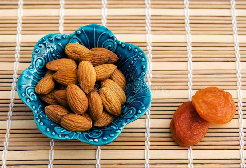 Amandes épluchées et quelques abricots de fruits secs image stock