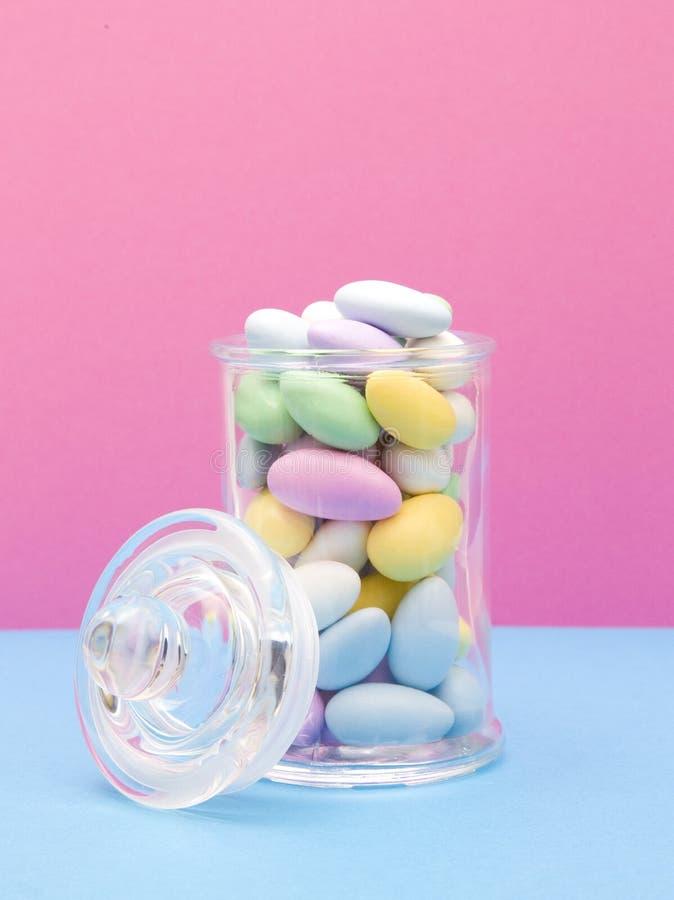 Amandes enduites de sucrerie sur un fond rose et bleu photo stock