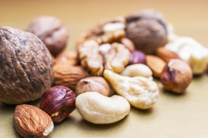 Amandes, noisettes, noix de cajou et noix entières sur le fond d'or Casse-croûte organique sain, petit déjeuner, ingrédients de n images stock
