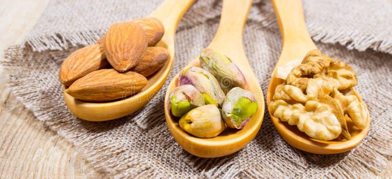 Amandes, noix et pistache sur une cuillère en bois photos stock