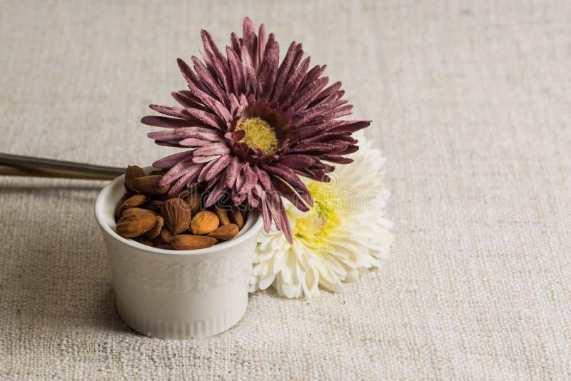 Amandes ?pluch?es dans une cuvette et des fruits secs blancs d'amandes sur la texture beige de tissu, d?coration de fleur, l'espa photos stock