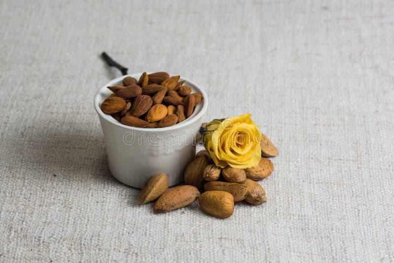 Amandes ?pluch?es dans une cuvette et des fruits secs blancs d'amandes sur la texture beige de tissu, d?coration jaune de fleur,  photos libres de droits
